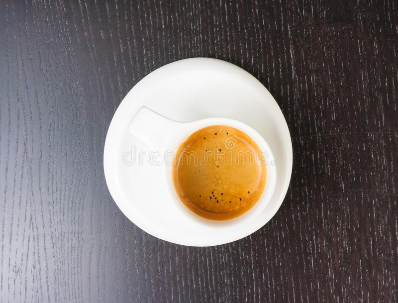 伟大的意大利咖啡看法上面在一个白色杯子的在黑木桌上 库存照片