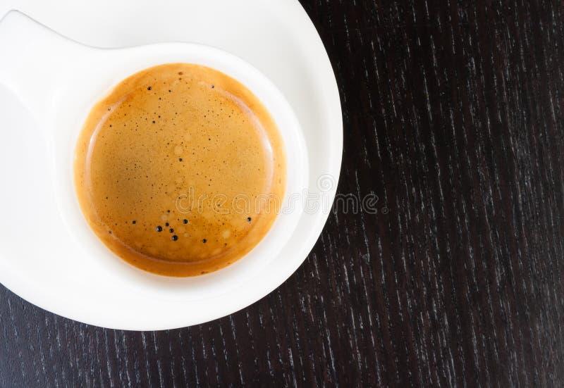伟大的意大利咖啡细节在一个白色杯子的在黑木桌上 库存图片
