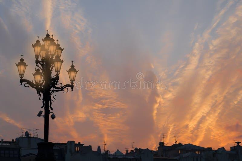 伟大的老路灯柱、城市屋顶和神秘的火热的日落 库存照片