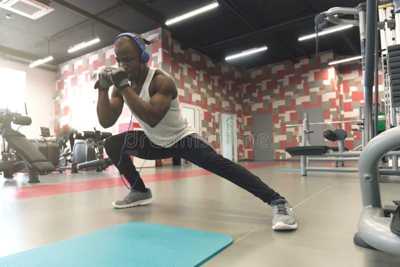 伟大舒展 年轻英俊的人侧视图做舒展在健身房的运动服的 库存照片