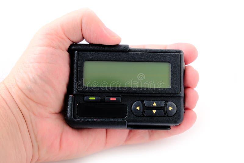 传呼器在白色背景隔绝的手上 免版税库存照片