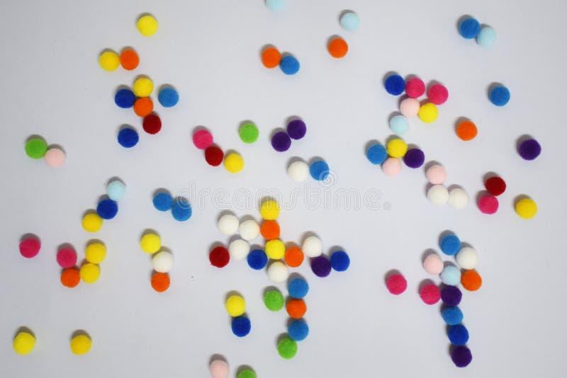 传播在白色背景的梯度甜颜色pom poms 免版税图库摄影