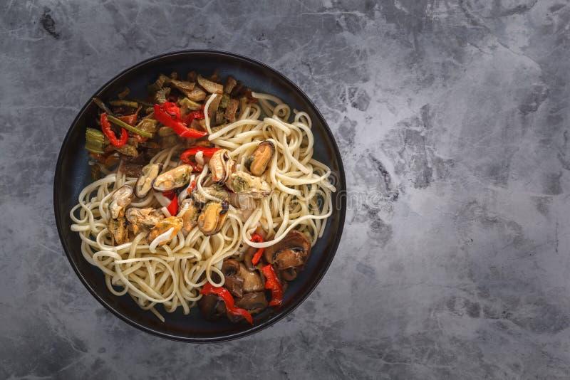 传统亚洲食物-面条用海鲜、沙拉、红辣椒和油煎的蘑菇在一张灰色桌上 免版税库存图片
