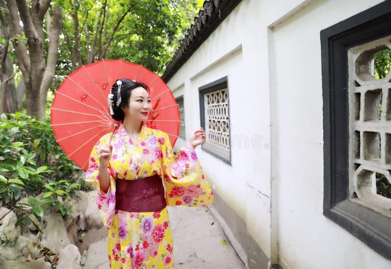 传统亚裔日本美丽的新娘艺妓在夏天自然庭院里女服和服举行一把白色红色伞 库存图片