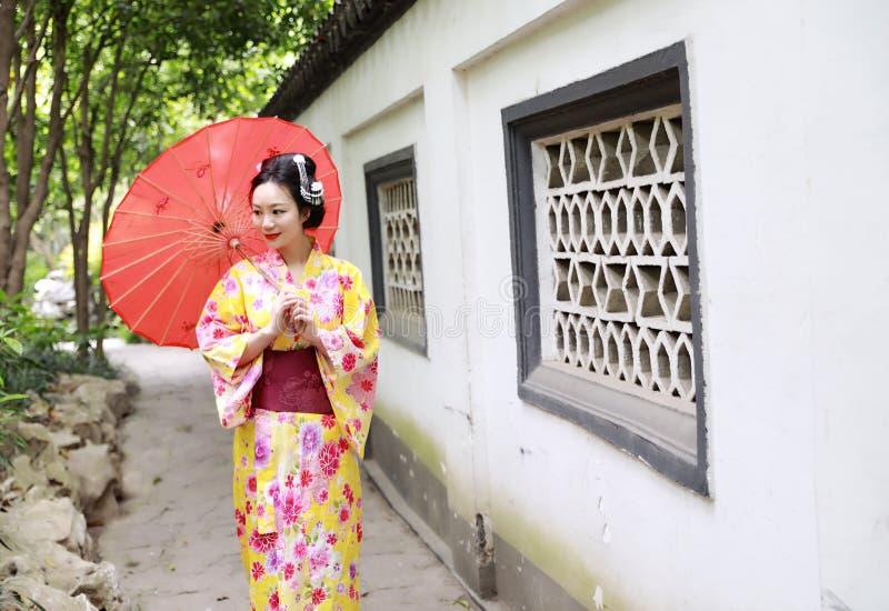 传统亚裔日本美丽的新娘艺妓在夏天自然庭院里女服和服举行一把白色红色伞 免版税库存照片