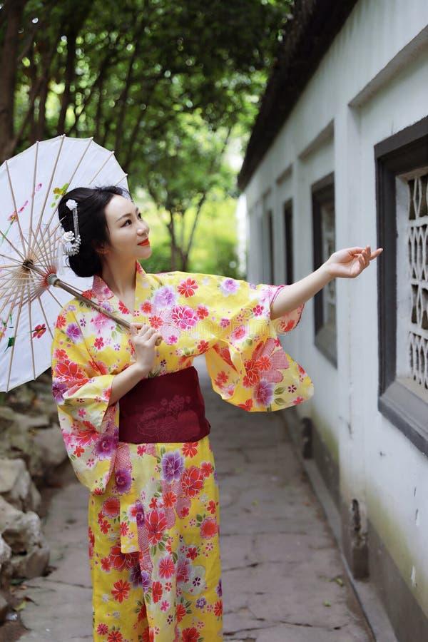 传统亚裔日本美丽的新娘艺妓在夏天自然庭院里女服和服举行一把白色红色伞 免版税图库摄影