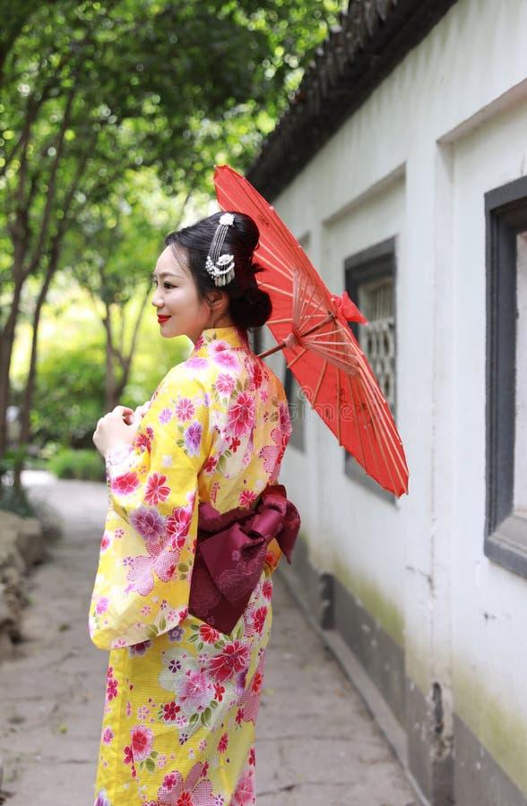 传统亚裔日本美丽的新娘艺妓在夏天自然庭院里女服和服举行一把白色红色伞 库存照片