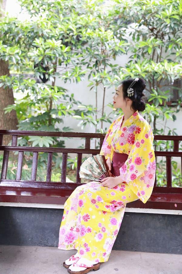 传统亚裔日本美丽的艺妓在夏天自然庭院里女服和服坐一条长凳 免版税库存图片
