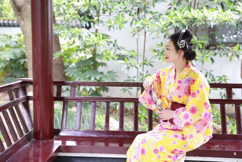 传统亚裔日本美丽的艺妓在夏天自然庭院里女服和服坐一条长凳 免版税库存照片