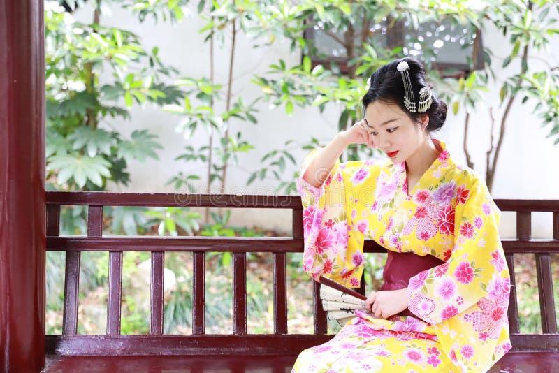传统亚裔日本美丽的艺妓女服爱好者坐一条长凳在夏天自然庭院里的和服举行 图库摄影