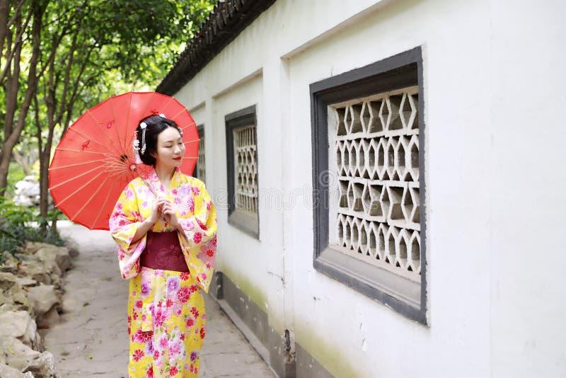 传统亚裔日本美丽的艺妓新娘在夏天自然庭院里女服和服举行一把伞 免版税图库摄影
