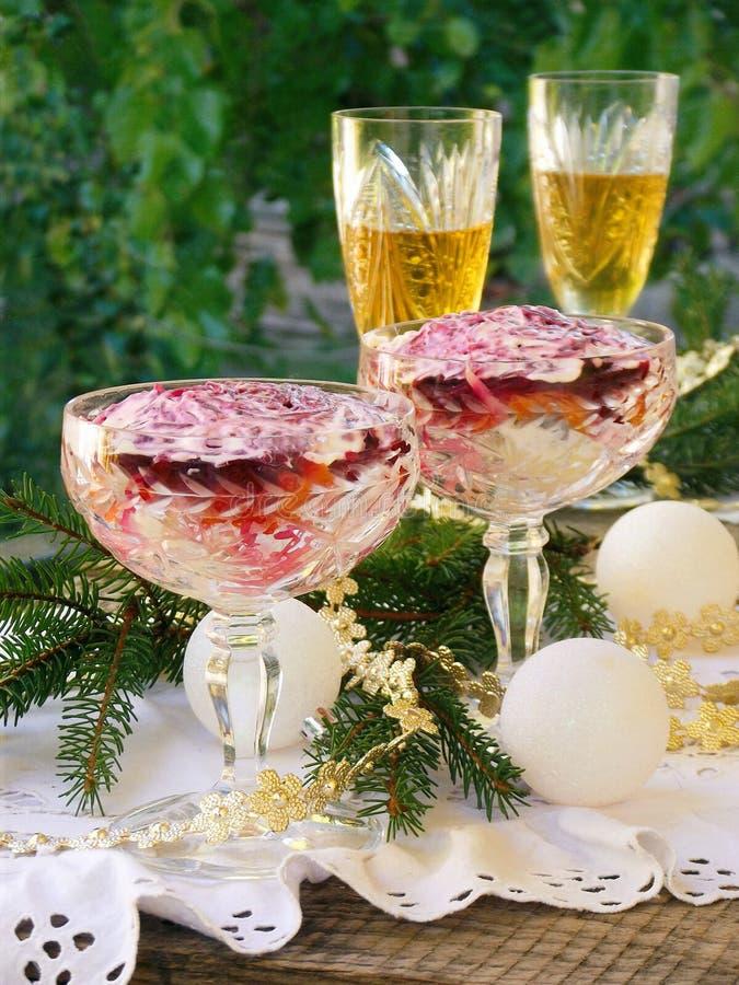 传统俄国新年` s沙拉鲱鱼和甜菜根源 层状菜和鱼沙拉 玻璃用香槟 有选择性 免版税图库摄影