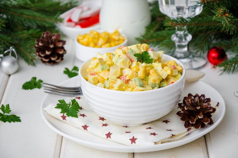 传统俄国沙拉用螃蟹棍子、新鲜的黄瓜、玉米和熟蛋在碗 库存照片