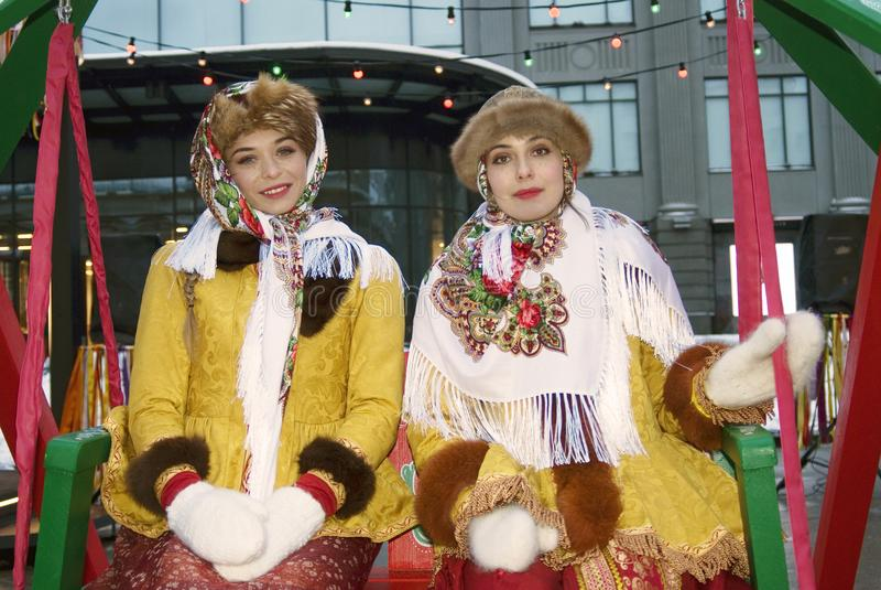 传统俄国衣裳的两个年轻美丽的夫人为照片摆在 免版税图库摄影