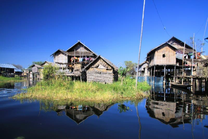 传统光滑的高跷木屋的反射作为玻璃水与无云的天空蔚蓝- Inle湖,缅甸形成对比 免版税图库摄影