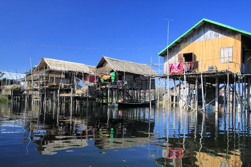 传统光滑的高跷木屋的反射作为玻璃水与无云的天空蔚蓝- Inle湖,缅甸形成对比 免版税库存图片