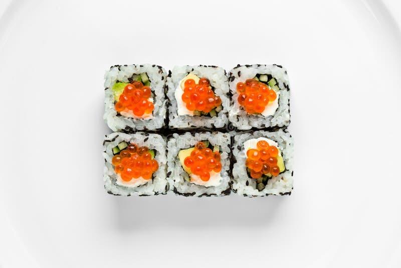传统加利福尼亚寿司卷用红色鱼子酱,在一张白色背景顶视图的黄瓜 库存图片