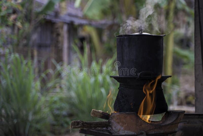 传统厨房,蒸罐-地方厨房的糯米在村庄 煮沸为在火的电饭锅的黑罐 免版税库存图片