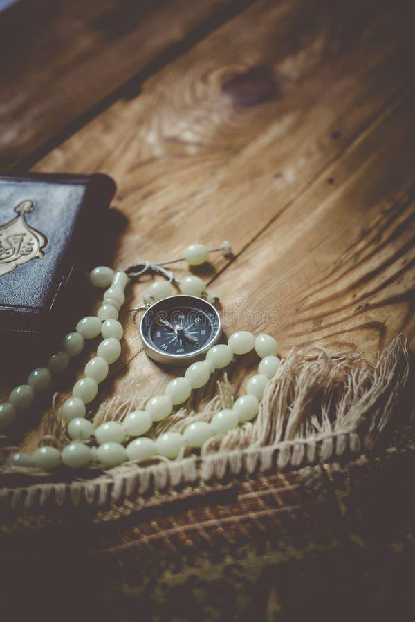 传统回教祷告集合捆绑 祈祷的地毯、念珠小珠、圣洁古兰经的小的版本和在木的qibla指南针 库存照片