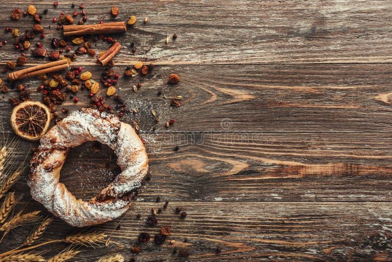 传统圆的脆煎肉片、干果子和麦子在土气木背景 顶视图,光线影响 库存图片