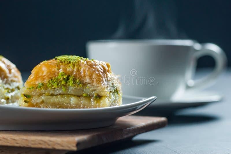 传统土耳其点心antep果仁蜜酥饼用在白色板材的开心果在粗麻布大袋 免版税库存图片