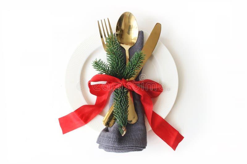传统圣诞节桌餐位餐具 金黄利器,亚麻布餐巾、绿色云杉的分支、板材和红色丝带 图库摄影