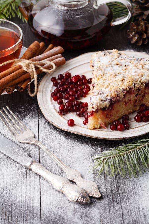 传统圣诞节蛋糕用干果子、葡萄干和一杯茶在一张木桌上的与圣诞装饰 库存图片