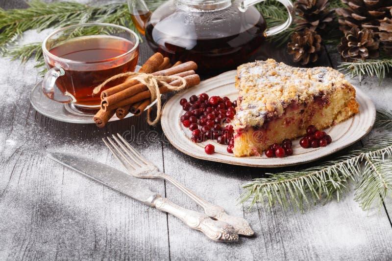 传统圣诞节蛋糕用干果子、葡萄干和一杯茶在一张木桌上的与圣诞装饰 库存照片