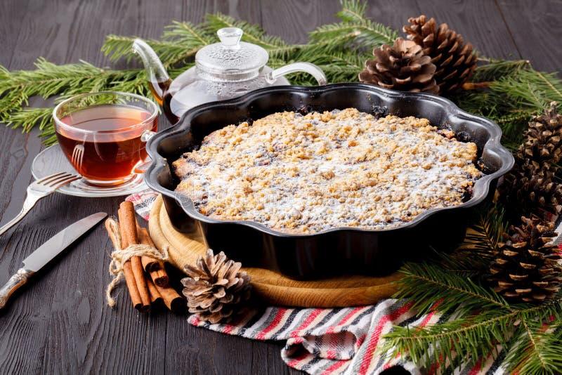传统圣诞节蛋糕用干果子、葡萄干和一杯茶在一张木桌上的与圣诞装饰 免版税图库摄影