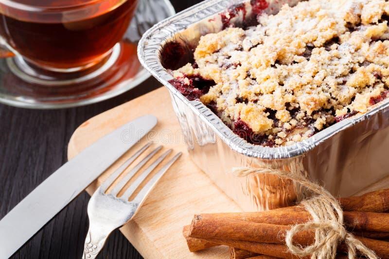 传统圣诞节蛋糕用干果子、葡萄干和一杯茶在一张木桌上的与圣诞装饰 免版税库存照片