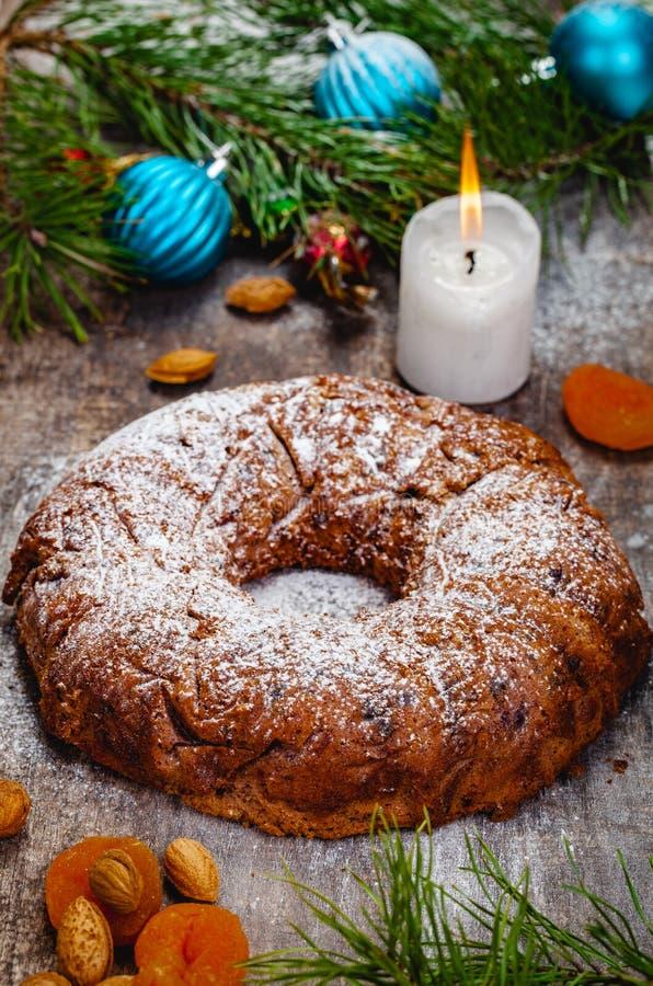 传统圣诞节蛋糕用干果子、葡萄干和坚果有圣诞装饰的在木背景 库存照片