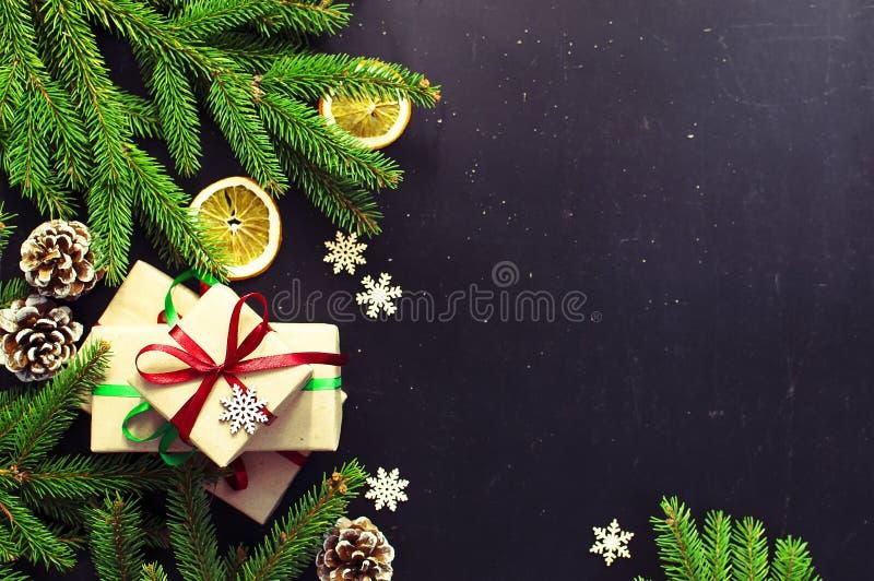 传统圣诞节黑暗的背景顶视图 新年构成云杉分支杉木锥体提出橙色雪花 库存照片