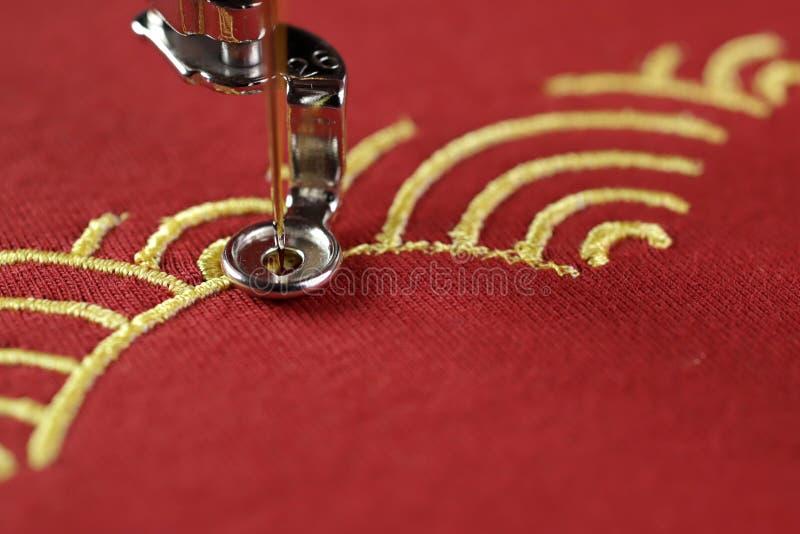 传统壳样式刺绣与金子的在刺绣机器-春节概念的红色织品 免版税图库摄影