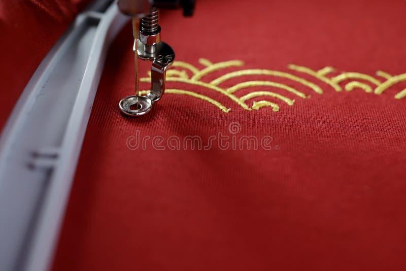 传统壳样式刺绣与金子的在现代刺绣机器做的红色织品-文本的拷贝空间 库存照片