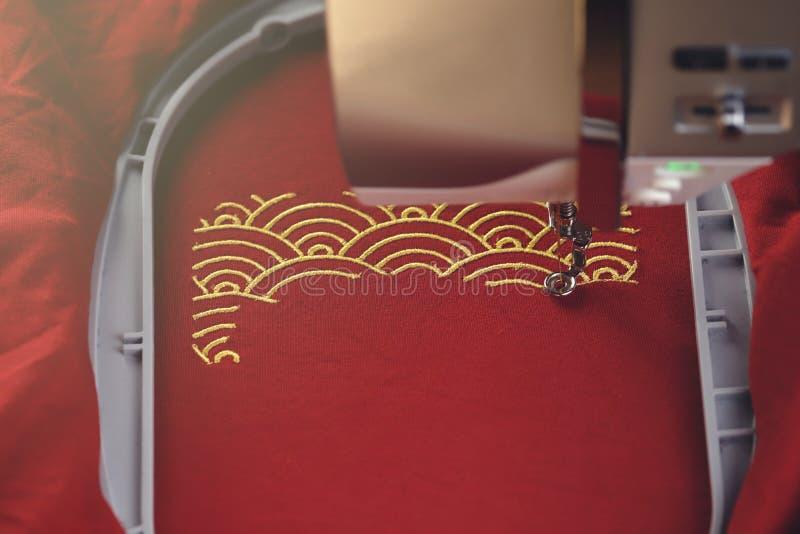 传统壳样式刺绣与金子的在红色织品-春节概念-在明亮的金黄光的机器头 免版税库存图片