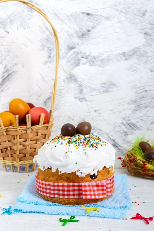 传统复活节蛋糕- kulich、朱古力蛋在巢和五颜六色的被绘的鸡蛋在木白色背景 免版税库存照片