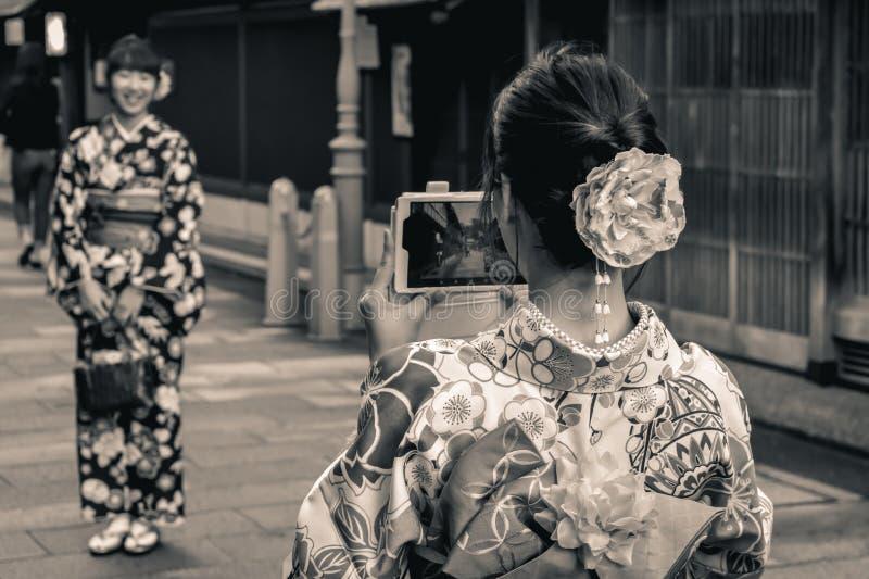传统夏天yukatas的日本女孩为照相的与前个技术手机在日本 库存照片