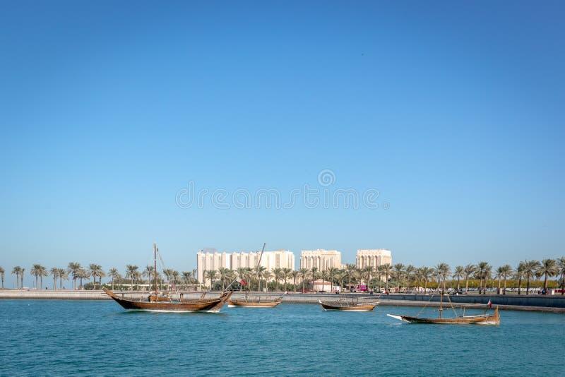 传统小船在有一些大厦的大海海在背景中在一蓝天天在多哈,卡塔尔 库存照片