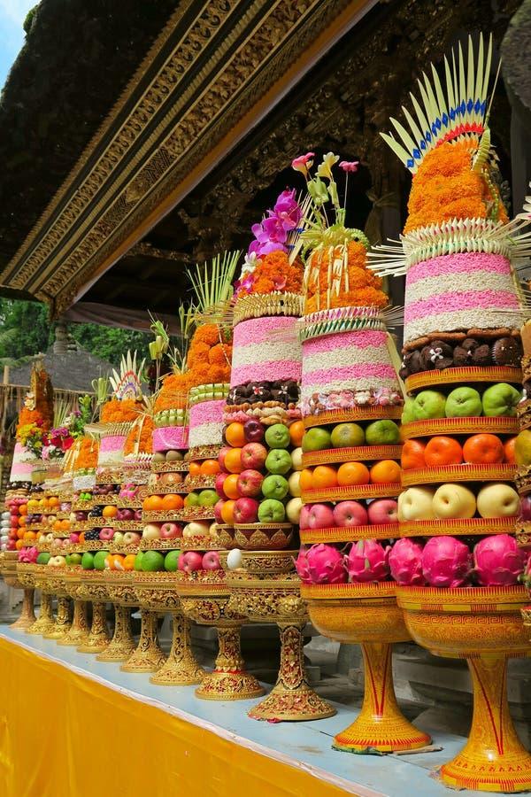 传统巴厘语礼仪寺庙奉献物:大果子和米金字塔在用花装饰的金黄板材 免版税库存照片