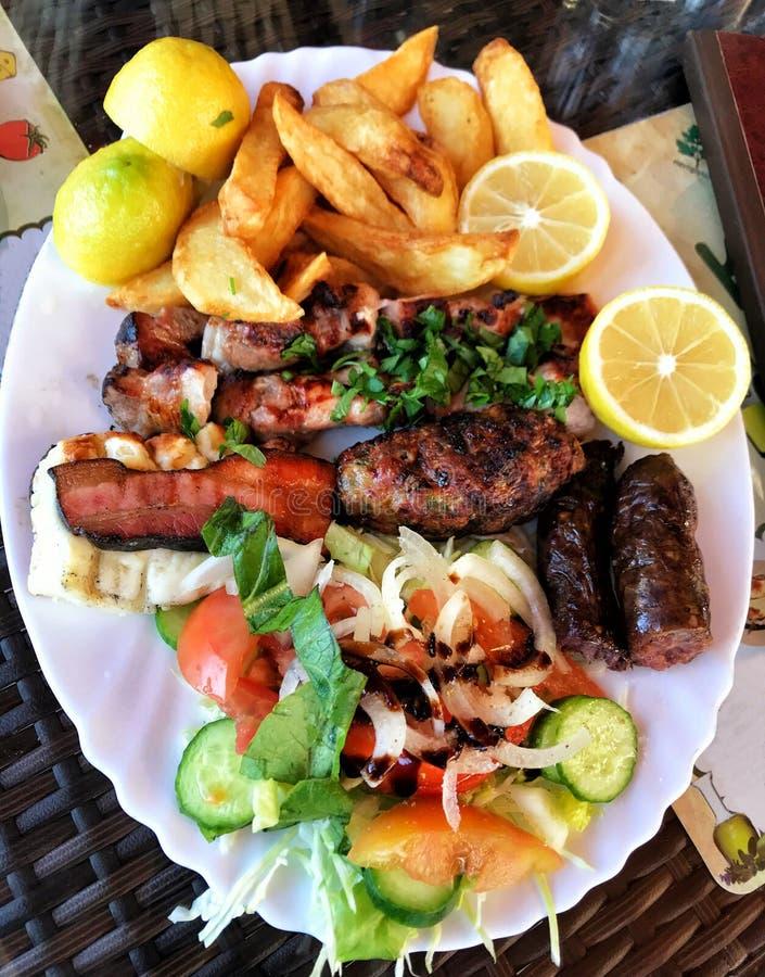 传统希腊肉souvlaki板材用土豆和沙拉 库存图片