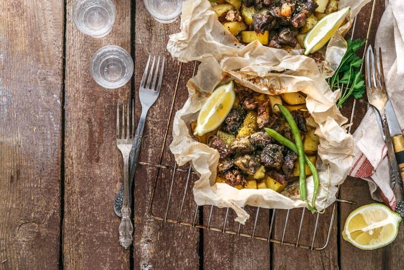 传统希腊kleftiko,一个被用烤箱烘的羊羔炖煮的食物用土豆,橄榄油,葱,红萝卜,大蒜和草本,服务与 免版税库存图片