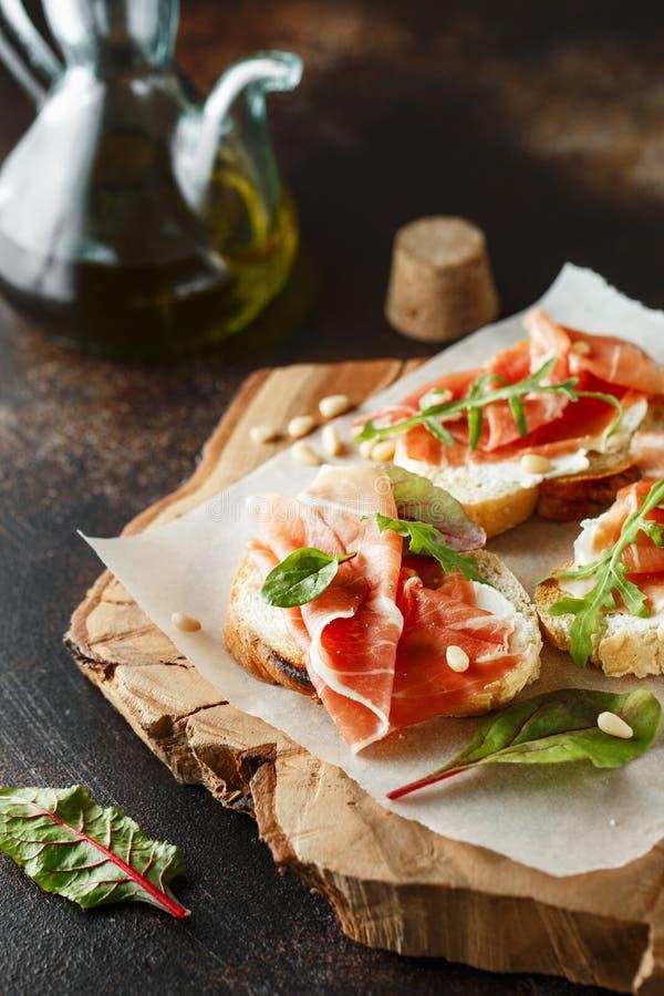 传统帕尔马治疗了火腿开胃小菜 Bruschetta设置了用帕尔马火腿和帕尔马干酪 与熏火腿的小三明治, 免版税库存照片