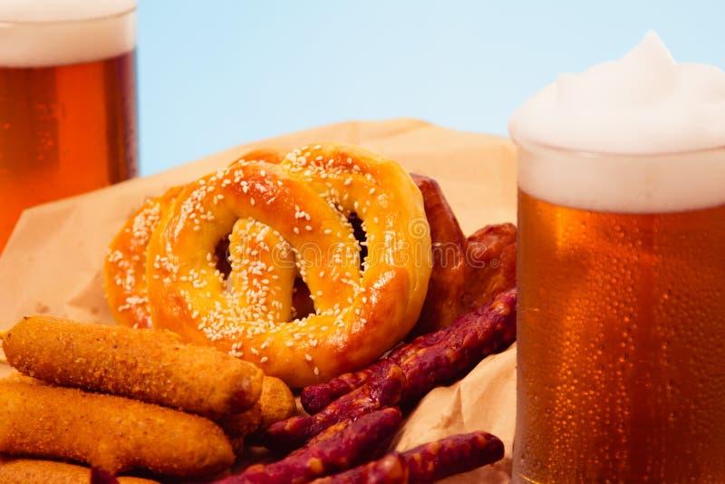 传统德国食物 杯子啤酒和可口烤香肠和炸薯条服务用在土气木桌上的面包小圆面包 库存图片