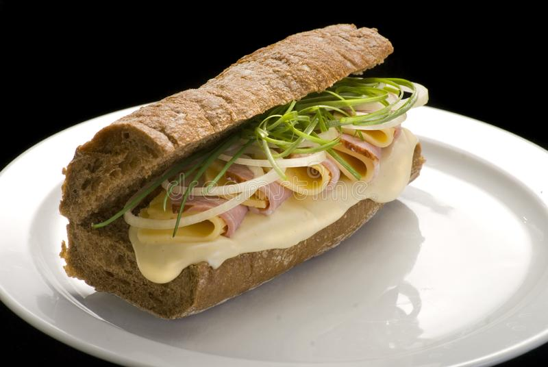 传统意大利三明治用火腿、乳酪和葱在一块白色板材 免版税库存照片