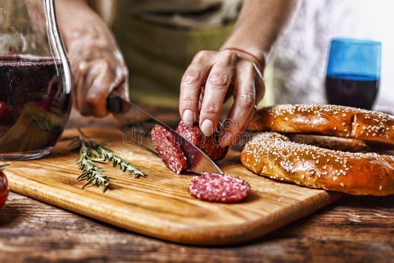 传统意大利红葡萄酒,蒜味咸腊肠,迷迭香,面包 关闭人` s手切开了在厨房板的蒜味咸腊肠 库存照片