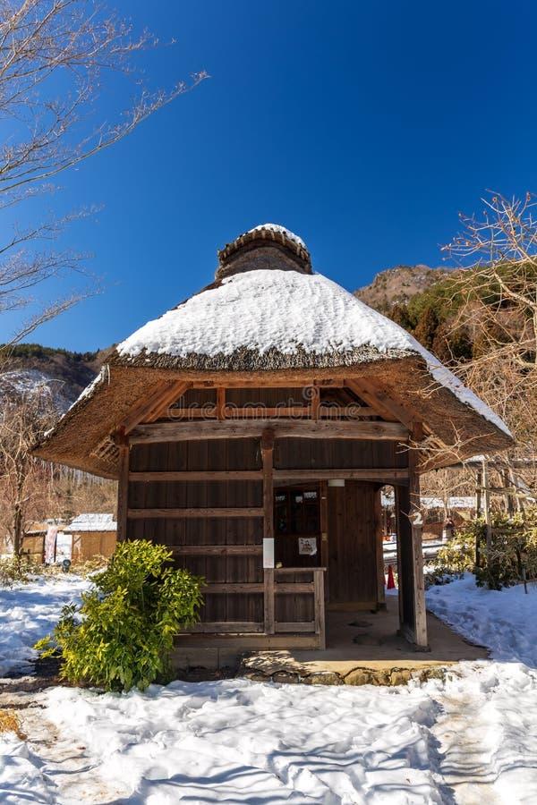 传统日本小茅屋顶房子在雪包括的Iyashino佐藤Nenba传统村庄在Saiko湖区域 库存照片