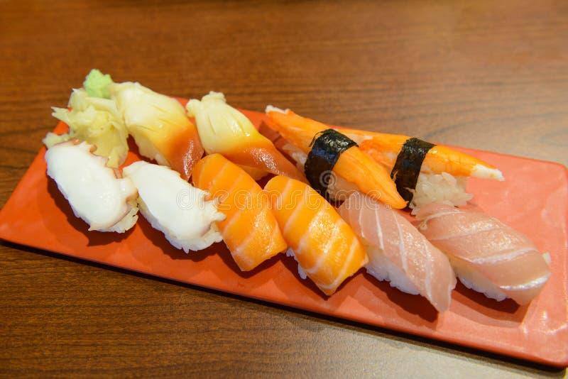 传统日本nigiri寿司设置了用乌贼,三文鱼,金枪鱼,在红色板材的螃蟹 免版税库存图片