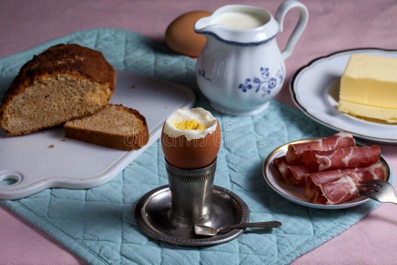 传统早餐:在一银色立场、黄油、烟肉、土气面包和鲜奶油的鸡蛋 免版税库存图片