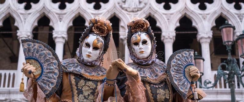 传统服装和被绘的面具的两名妇女,当装饰的爱好者,站立在共和国总督宫殿前面在威尼斯Carni期间 免版税库存图片
