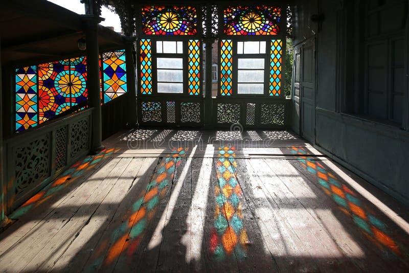 传统格鲁吉亚样式的木被雕刻的阳台与彩色玻璃窗 免版税库存照片